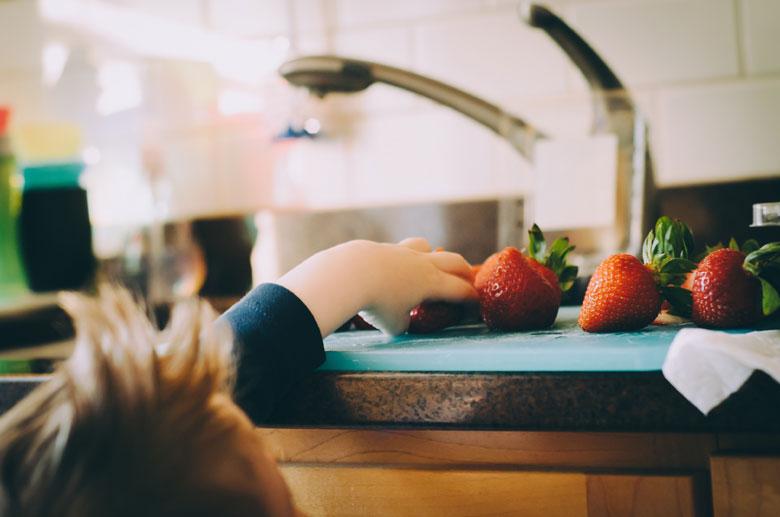 イチゴを取ろうとする幼児の手